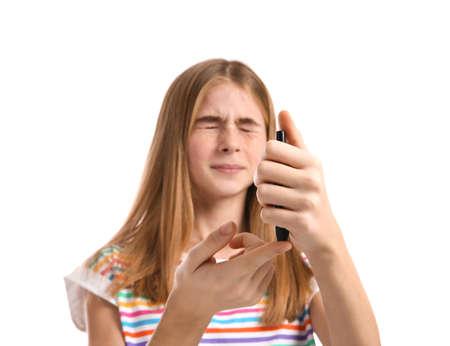 Teen girl using lancet pen on white background. Diabetes control