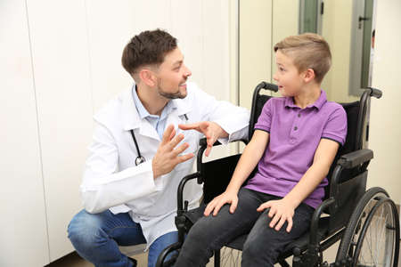 Doctor and little child in wheelchair at hospital