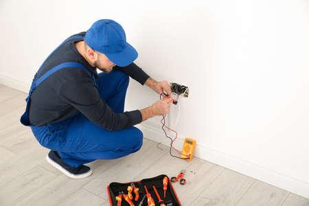 Electricista con comprobador de voltaje en interiores, espacio para texto