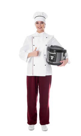 Full length portrait of female chef with modern multi cooker on white background