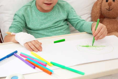 Little child with infusion drip drawing in hospital bed, closeup