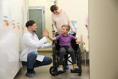 Doctor with woman and her child in wheelchair at hospital