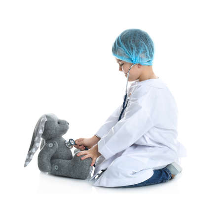 Cute child playing doctor with stuffed toy on white background
