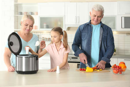 Mature couple and their granddaughter preparing food with modern multi cooker in kitchen