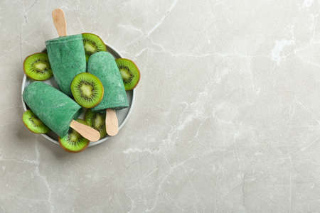 Plate with delicious spirulina and kiwi ice creams on grey background, top view. Space for text