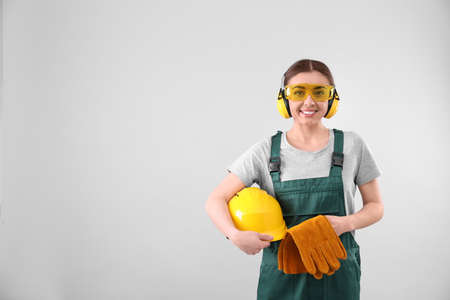 Female industrial worker in uniform on light background, space for text. Safety equipment