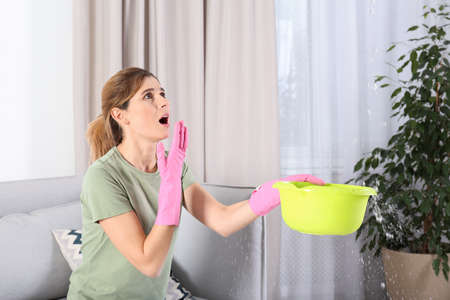 Woman collecting leaking water from ceiling in living room. Time to call plumber Archivio Fotografico