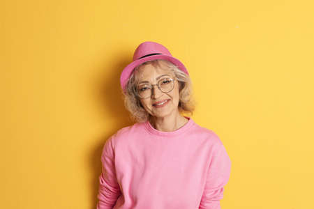 Portrait of mature woman in hipster outfit on color background Stock Photo