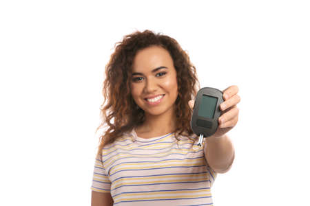 Young African-American woman holding glucometer on white background. Diabetes control