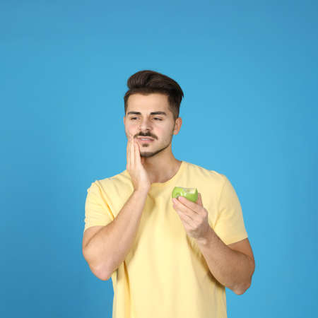 Emotional young man with sensitive teeth and apple on color background Stock Photo