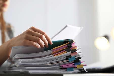 Büroangestellter, der mit Dokumenten am Tisch arbeitet, Nahaufnahme