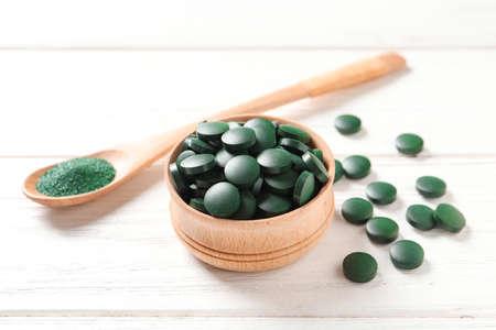 Bowl of spirulina pills and powder in spoon on wooden background Standard-Bild - 118223350