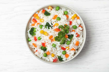 Bowl with tasty rice and vegetables on wooden background, top view