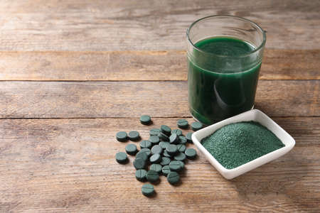 Spirulina powder, pills and drink on wooden background, space for text Stock Photo