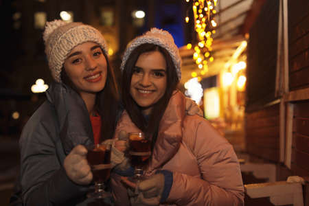 Friends with glass cups of mulled wine at winter fair