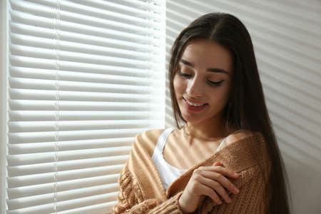 Young woman near window with Venetian blinds. Space for text