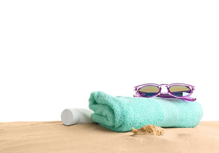 Composition with beach sand, sunglasses and towel on white background, space for text