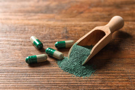 Scoop of spirulina powder and pills on wooden table Stock Photo