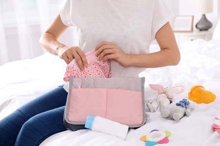 Woman packing baby accessories into maternity bag on bed, closeup