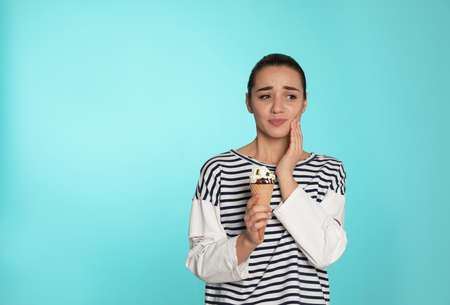 Emotional young woman with sensitive teeth and ice cream on color background. Space for text