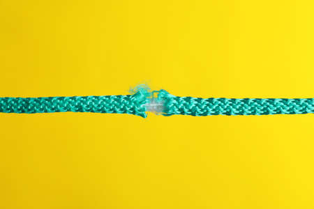 Rupture of blue rope on color background