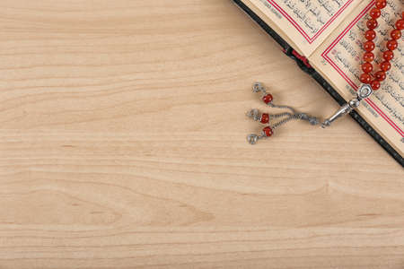 Muslim prayer beads, Quran and space for text on wooden background, top view Imagens