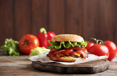 Tasty burger with bacon on wooden table. Space for text Фото со стока