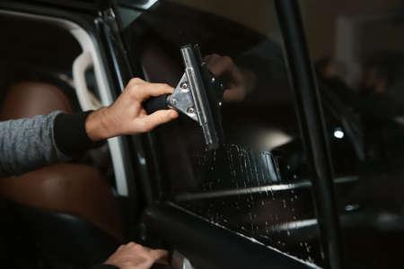 Worker washing car window before tinting in shop, closeup Фото со стока