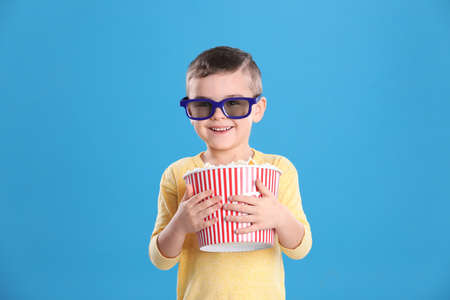 Cute little boy with popcorn and glasses on color background