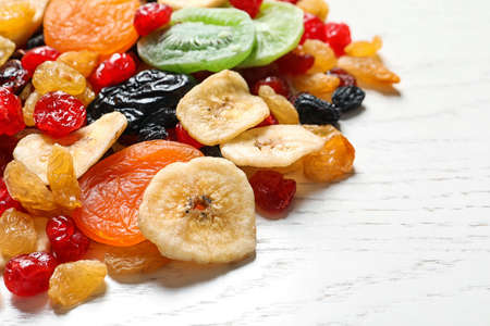 Different dried fruits on wooden background, space for text. Healthy lifestyle