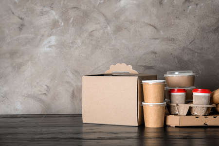Various takeout containers on table, space for text. Food delivery service