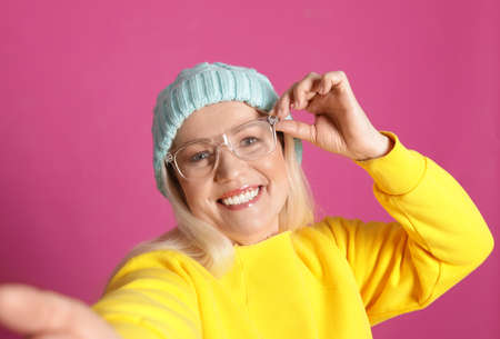 Mature woman in hipster outfit taking selfie on color background Archivio Fotografico