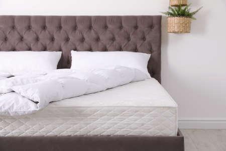 Wygodne łóżko z nowym materacem w pokoju. Zdrowy sen