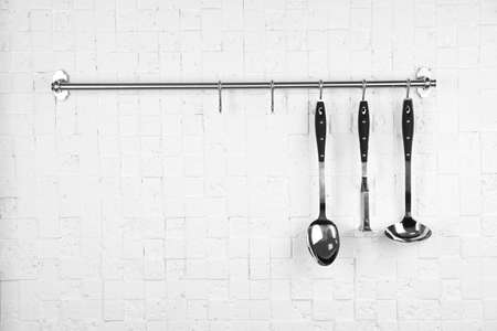 Rack with clean kitchen utensils on white white wall. Space for text Stock fotó