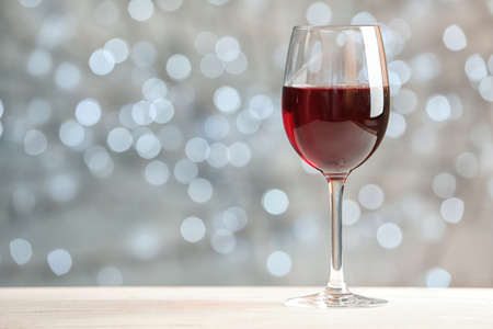 Glass of wine on table against blurred lights, space for text