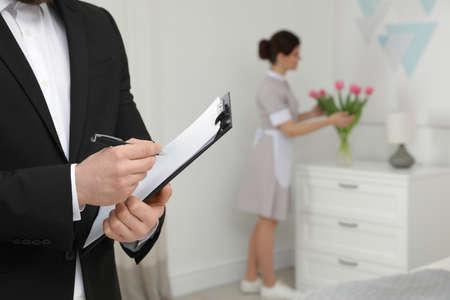 Housekeeping manager checking maid work in hotel room, closeup 版權商用圖片
