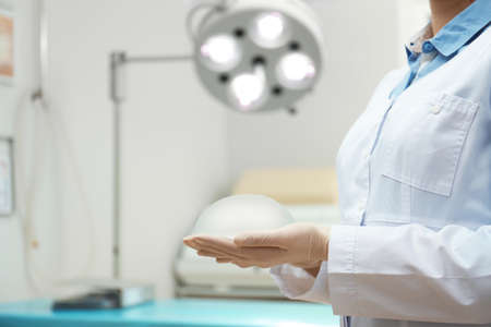 Doctor holding silicone implant for augmentation in clinic, closeup with space for text. Cosmetic surgery Archivio Fotografico
