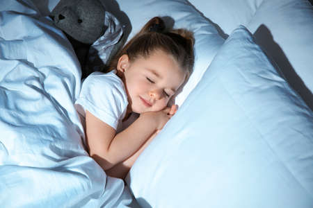 Beautiful little girl sleeping with toy in bed at night. Bedtime schedule