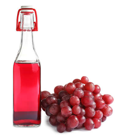 Bottle with wine vinegar and fresh grapes on white background Archivio Fotografico