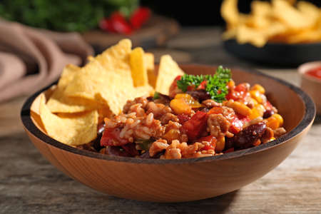 Tasty chili con carne served with tortilla chips in bowl on table Imagens