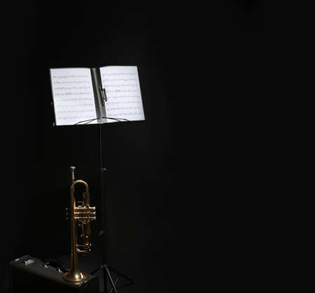 Trumpet, case and note stand with music sheets on black background. Space for text