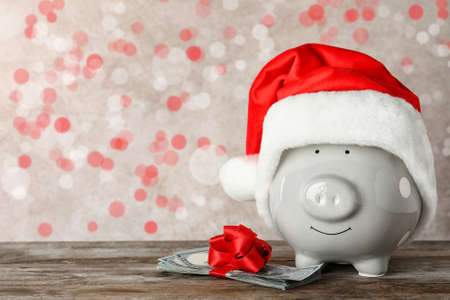 Cute piggy bank with Santa hat and dollar banknotes on table, space for text. Bokeh effect 版權商用圖片