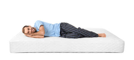 Young man lying on mattress against white background
