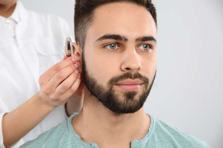 Otolaryngologist putting hearing aid in man's ear on white background
