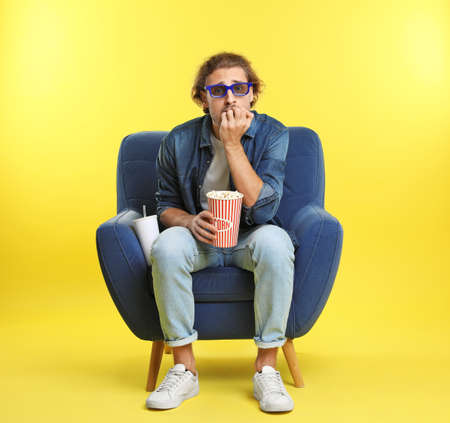 Emotional man with 3D glasses, popcorn and beverage sitting in armchair during cinema show on color background