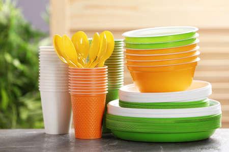 Nouvelle vaisselle en plastique sur table sur fond flou. Réglage de la table