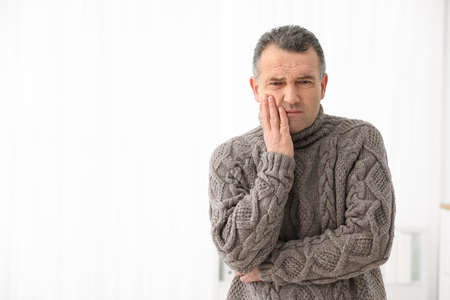 Hombre maduro que sufre de un fuerte dolor de muelas sobre un fondo claro, espacio para texto Foto de archivo