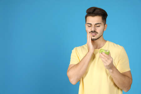Emotional young man with sensitive teeth and apple on color background. Space for text