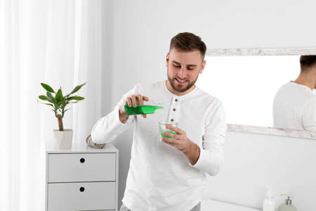 Young man with mouthwash in bathroom. Teeth and oral care Stock Photo
