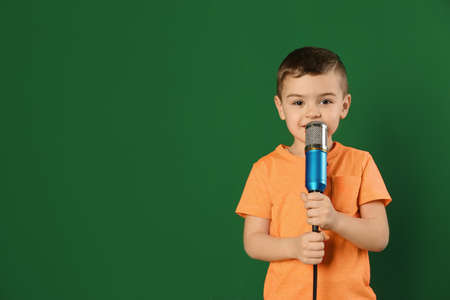 Cute funny boy with microphone on color background. Space for text Imagens